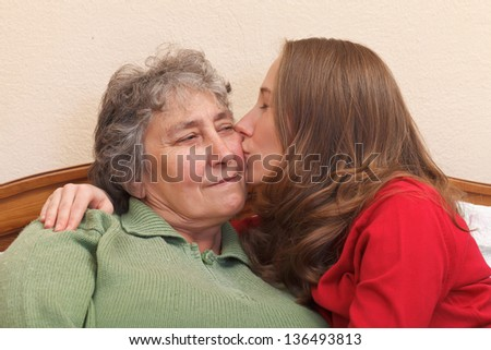 Kiss and hug for my mom and she feels happy - stock photo