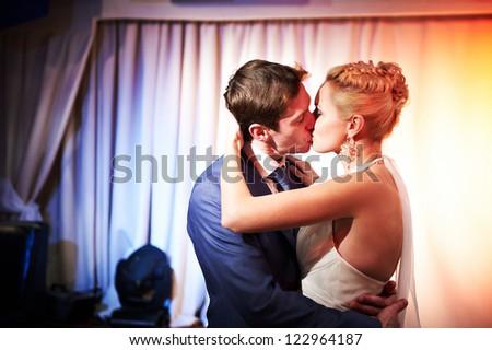 Kiss bride and groom on wedding dance - stock photo