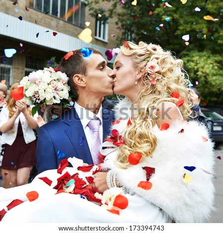 Kiss happy newlyweds and flying red and white petals - stock photo