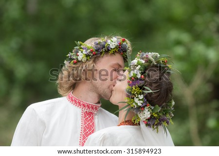 Kiss of the newlyweds in traditional wreaths - stock photo