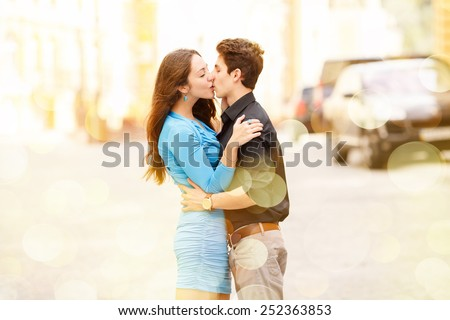 Kiss of two lovers in the city. Walking through the city. Love between two people. Honeymoon. Love story. Young happy couple in the city. Young man and beautiful woman on street. Spend their holidays. - stock photo