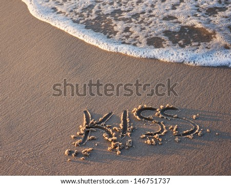 kiss word written on the sand at the evening - stock photo