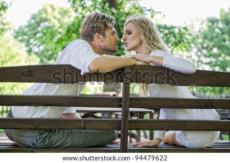 Kissing couple on the bench - stock photo