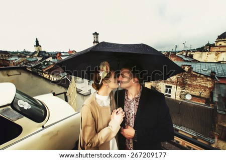 kissing fashion young couple under the umbrella  - stock photo