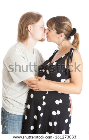 kissing happy young pregnant woman and her husband - stock photo