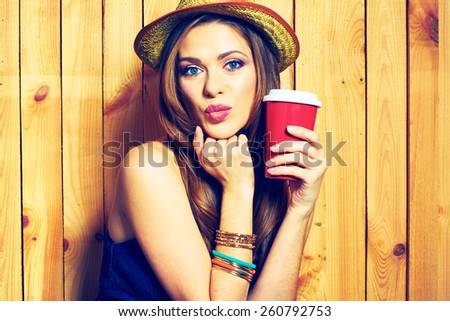 Kissing Hipster Girl Holding Coffee Cup. Yellow hat.Female  model with long hair. Beauty Face Portrait against wooden background. - stock photo