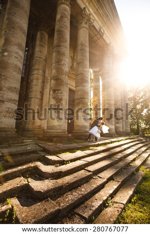 kissing on the stairs on the background castle - stock photo