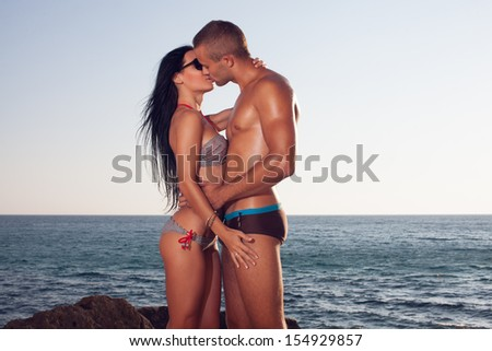 Kissing sporty couple on the beach. perfect bodies passion. The sea or ocean background. Love concept - stock photo