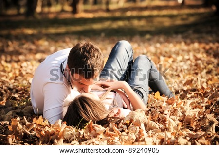 Kissing young couple in love in the autumn park - stock photo