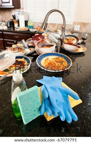 Kitchen and dish washing cleaning supplies ready to be used on dirty, filthy dishware. - stock photo