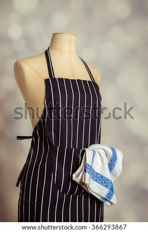 Kitchen apron on vintage mannequin with cloth - stock photo