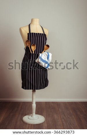 Kitchen apron on vintage mannequin with cooking utensils - stock photo