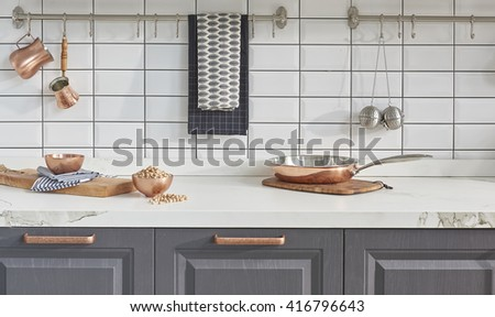 Kitchen brass utensils, chef accessories. Hanging copper kitchen with white tiles wall - stock photo