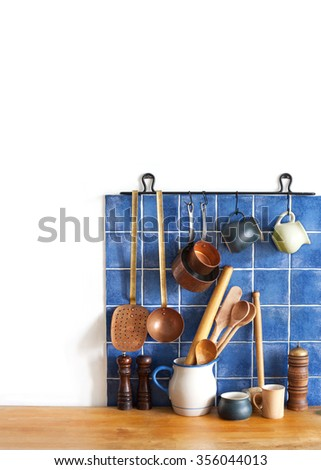 Kitchen brass utensils, chef accessories. Hanging copper kitchenware set. Spoon, skimmer, grater. Blue tiles ceramic wall. spoon, pitchers, spices on the wooden table. White background. copy space. - stock photo