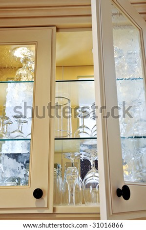 Kitchen cabinet close up with glass shelves and glasses - stock photo