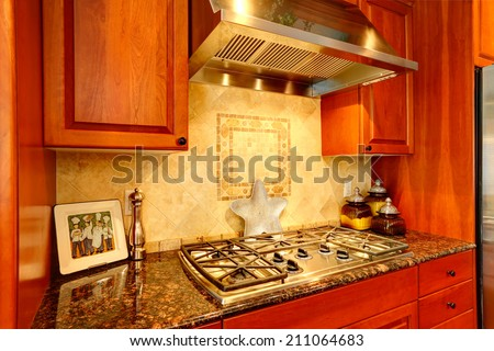 Kitchen cabinet with granite top and built-in stove. View of tile back splash trim - stock photo