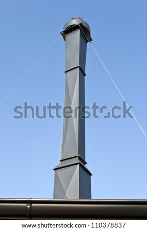 Kitchen chimney over blue sky - stock photo