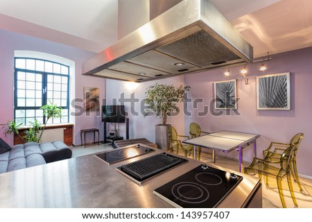 Kitchen connected with modern living room in loft apartment - stock photo