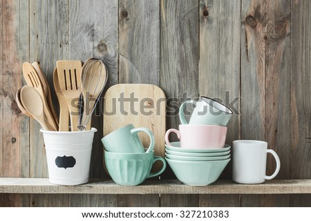 Kitchen cooking utensils in ceramic storage pot on a shelf on a rustic wooden wall - stock photo