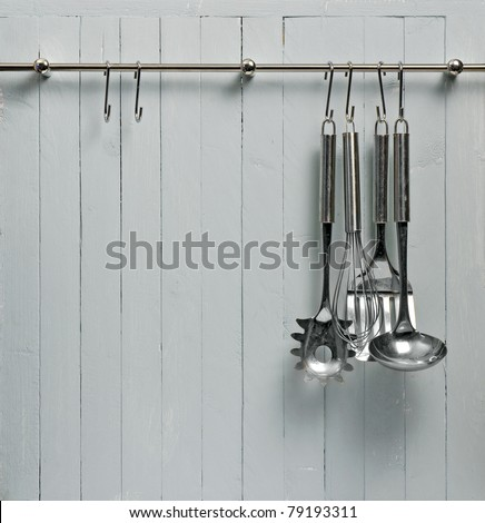 Kitchen cooking utensils on steel rack; steel spatulas etc against rustic wooden wall; good copy-space - stock photo