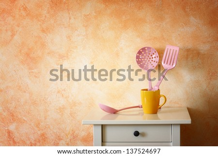 Kitchen cooking utensils. plastic spatulas in yellow cup against rustic terracotta wall. - stock photo