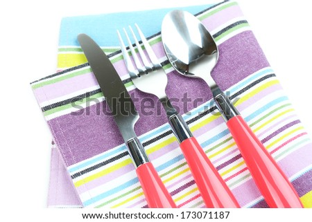Kitchen cutlery on color napkin close up - stock photo
