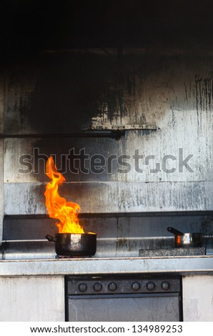 Kitchen fire in pot. Concept photo of Unattended cooking, risk of fire, fire kitchen and danger at home and prevention, cooking safety. - stock photo