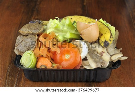 Kitchen food waste, vegetables, tea bags and fruit collected in re-used packaging, for home composting. - stock photo