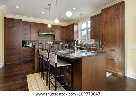 Kitchen in luxury home with oak wood cabinetry - stock photo