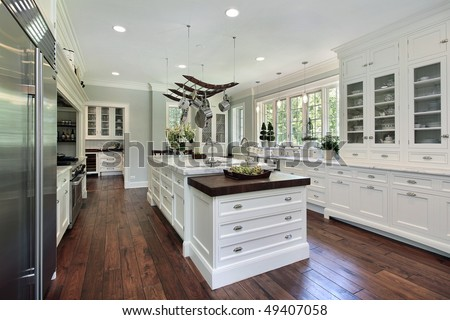 Kitchen in luxury home with white cabinetry - stock photo