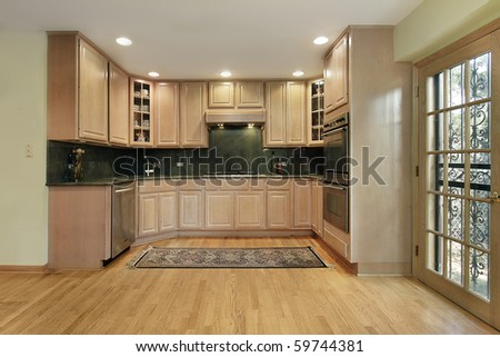 Kitchen in remodeled home with oak wood cabinetry - stock photo