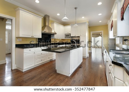 Kitchen in remodeled home with white cabinetry - stock photo