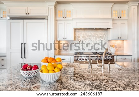 Kitchen Interior Detail in New Luxury Home with Island, Sink, Cabinets, and Bowls of Fruit - stock photo
