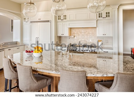 Kitchen Interior in New Luxury Home with Island, Sink, Cabinets, and Hardwood Floors - stock photo