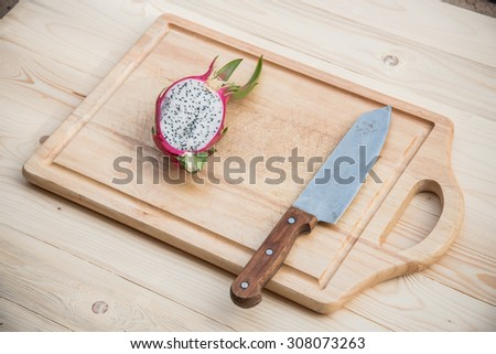 Kitchen Knife and Dragon Fruit on a wooden - stock photo