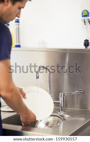 Kitchen porter cleaning plates in sink in professional kitchen - stock photo