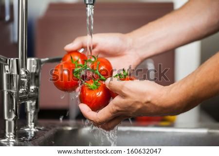 Kitchen porter washing tomatoes in professional kitchen - stock photo