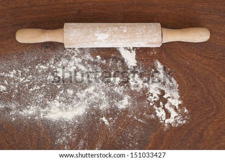 Kitchen rolling pin, flour on wooden background  - stock photo
