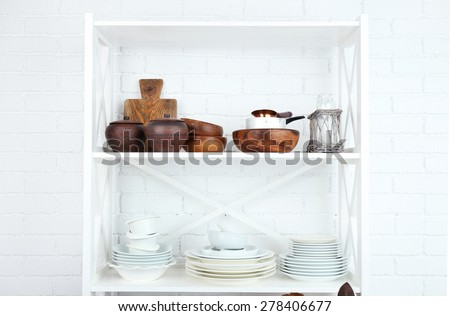 Kitchen shelving with dishes on white brick wall background - stock photo