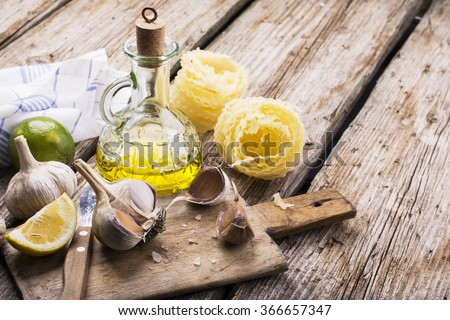 Kitchen simple still life of pasta, olive oil, fresh garlic, herbs and grasses on a simple wooden cutting board. The concept is simply great home cooking. selective Focus - stock photo