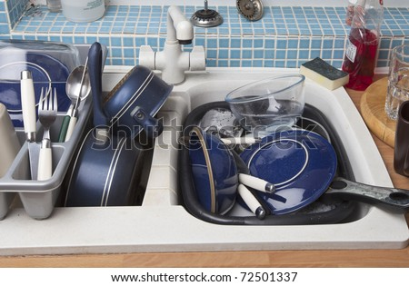 kitchen sink full of dirty dishes for washing up - stock photo
