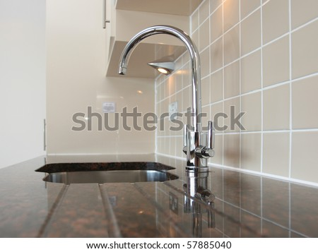 Kitchen sink with mixer tap recessed into granite work surface. - stock photo