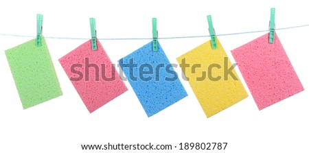 Kitchen sponges hanging on rope isolated on white - stock photo