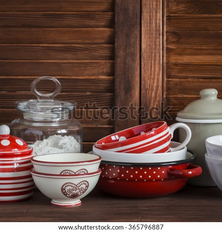 Kitchen still life. Vintage crockery - jar of flour, ceramic bowls, pan, enamelled  jar,  gravy boat. On a dark brown wooden table. Vintage and rustic style - stock photo