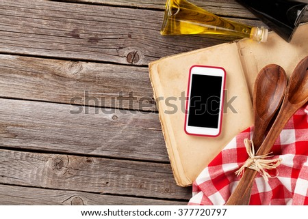 Kitchen table with ingredients, utensils and smartphone with blank screen for your app over cooking book on wooden table. Top view with copy space - stock photo