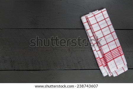 Kitchen towel red on black wooden background. - stock photo