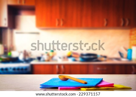 Kitchen towels and wooden spoons on the table - stock photo