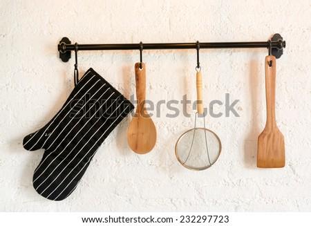 kitchen utensil hang on white stone wall - stock photo