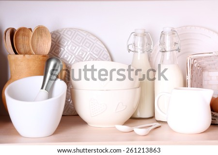Kitchen utensils and tableware on shelf - stock photo