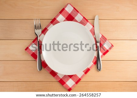 kitchen utensils at cloth napkin on wooden background - stock photo